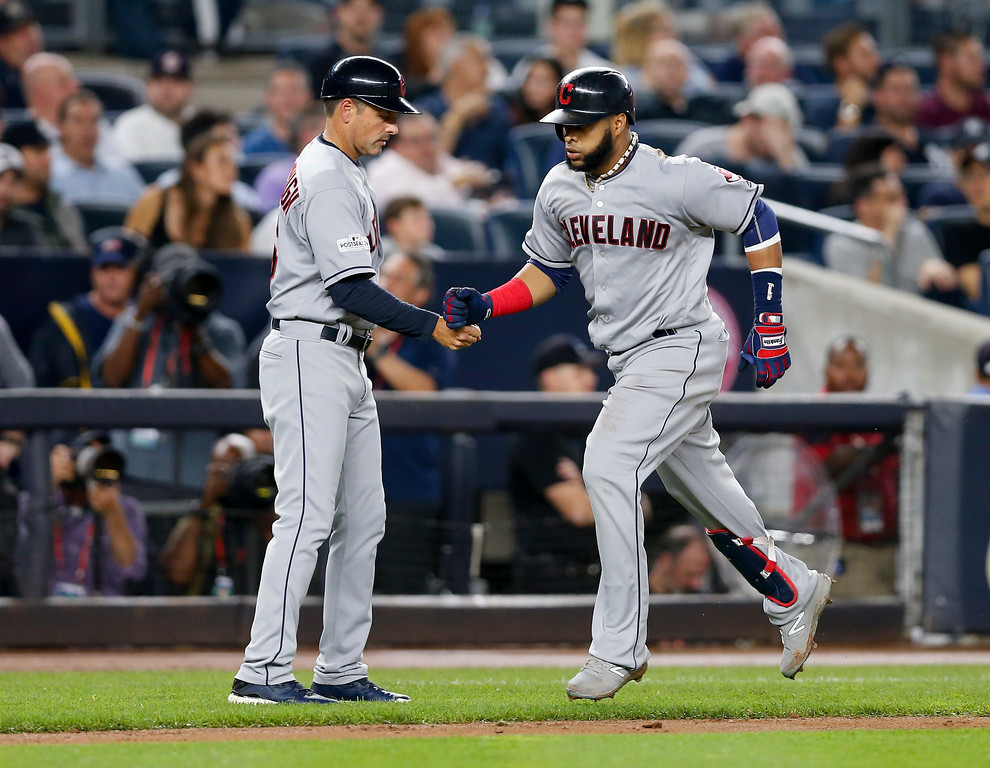 . Cleveland Indians\' Carlos Santana, right, is congratulated by third base coach Mike Sarbaugh after hitting a two-run home run against the New York Yankees during the fourth inning in Game 4 of baseball\'s American League Division Series, Monday, Oct. 9, 2017, in New York. (AP Photo/Kathy Willens)