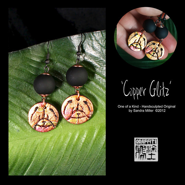 """COPPER GLITZ EARRINGS  Small and glitzy, these hand sculpted earrings feature black round matte finished beads hinged to iridescent copper chow heads.  A lot of impact in a very small space!  EARRINGS MEASURE 1 1/2"""" long x1/2"""" wide without wire"""
