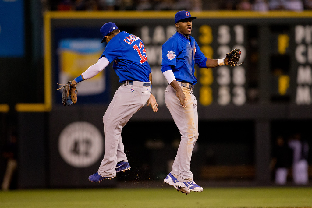 . DENVER, CO - JULY 19:  Starlin Castro #13 and Junior Lake #21 of the Chicago Cubs celebrate after defeating the Colorado Rockies 3-1 at Coors Field on July 19, 2013 in Denver, Colorado.  Lake made went 3-4 in his Major League debut. (Photo by Justin Edmonds/Getty Images)