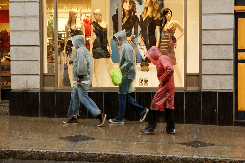 Pedestrians walking in rain. Rue Saint-Jean, Quebec City, Canada.