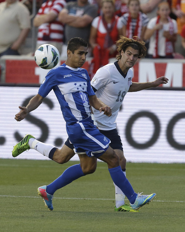 . United State\'s Graham Zusi (19) passes the ball while Honduras\' Jorge Claros (20) looks on in the second half during an World Cup qualifying soccer match at Rio Tinto Stadium on Tuesday, June 18, 2013, in Sandy, Utah.  (AP Photo/Rick Bowmer)