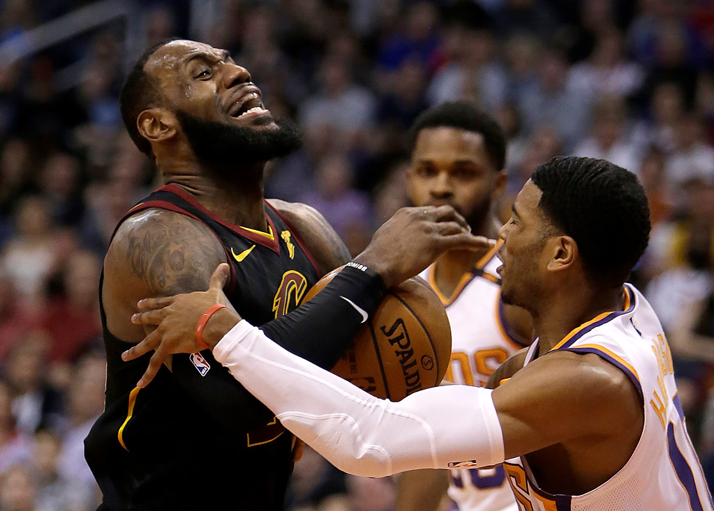 . Cleveland Cavaliers forward LeBron James (23) gets fouled by Phoenix Suns guard Shaquille Harrison in the first half during an NBA basketball game, Tuesday, March 13, 2018, in Phoenix. (AP Photo/Rick Scuteri)