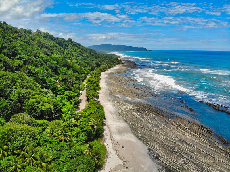 Lush Tropical Beach Paradise with blue water, great waves and rock formations in Malpais / Santa Teresa, Nicoya Peninsula Costa Rica