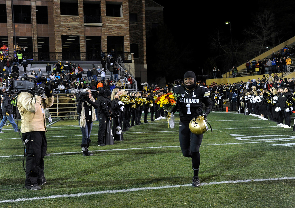 . BOULDER, CO - NOVEMBER 23: With loud cheers after the announcement of his name, senior Derrick Webb, a linebacker for the Colorado Buffaloes football team, runs on to Folsom Field with a bouquet of flowers intended for his mother, Felicia Morris, before the start the game against the Southern California Trojans at Folsom Field in mid-November. It is senior day and the last home game of the season, and each senior player is recognized and greeted by family and friends on the field. (Photo by Kathryn Scott Osler/The Denver Post)