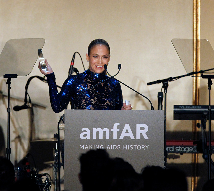 . Jennifer Lopez holds up her Humanitarian Award during the 4th Annual amfAR Inspiration Gala at the Plaza Hotel in New York, USA, 13 June 2013. The charity event benefits the Foundation\'s AIDS research programs.  EPA/JASON SZENES