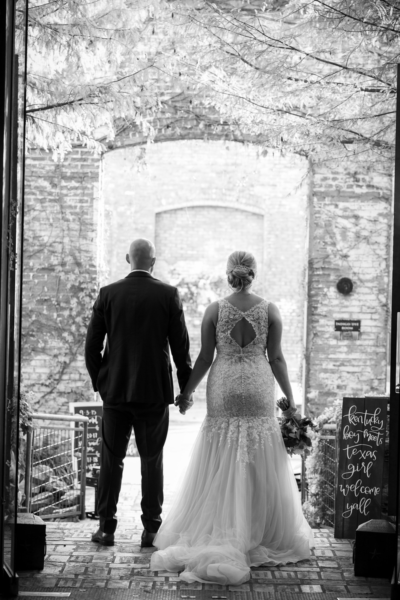 bride and groom holding hands with their backs to the camera