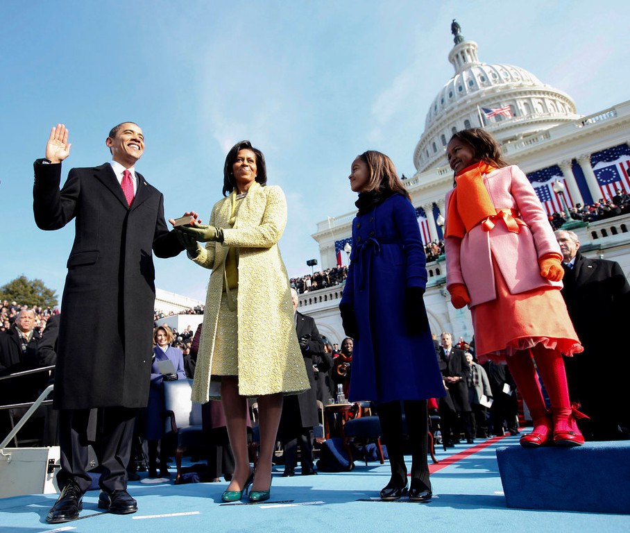 . FILE - This Jan. 20, 2009 file photo shows Barack Obama, left, taking the oath of office from Chief Justice John Roberts, not seen, as his wife Michelle, holds the Lincoln Bible and daughters Sasha, right and Malia, look on at the U.S. Capitol in Washington. Michelle Obama is wearing a yellow sheath and coat by Isabel Toledo. Michelle Obama has proven her fashion savvy time and time again since she was introduced to the country as first lady on Inauguration Day 2009. In the past four years she has adeptly walked the line between directional fashionista and everywoman. (AP Photo/Chuck Kennedy, Pool, file)