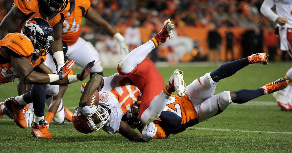 . Kansas City Chiefs running back Jamaal Charles (25) is tackled by Denver Broncos strong safety Mike Adams (20) during the second quarter. The Denver Broncos vs. the Kansas City Chiefs at Sports Authority Field at Mile High in Denver on November 17, 2013. (Photo by Tim Rasmussen/The Denver Post)