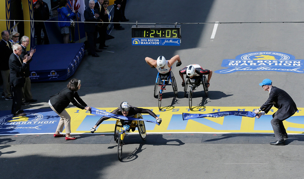 . Marcel Hug, of Switzerland, breaks the tape ahead of Kurt Fearnley, of Australia, center, and Ernst Van Dyk, of South Africa, in the wheelchair division of the 120th Boston Marathon on Monday, April 18, 2016, in Boston. (AP Photo/Charles Krupa)