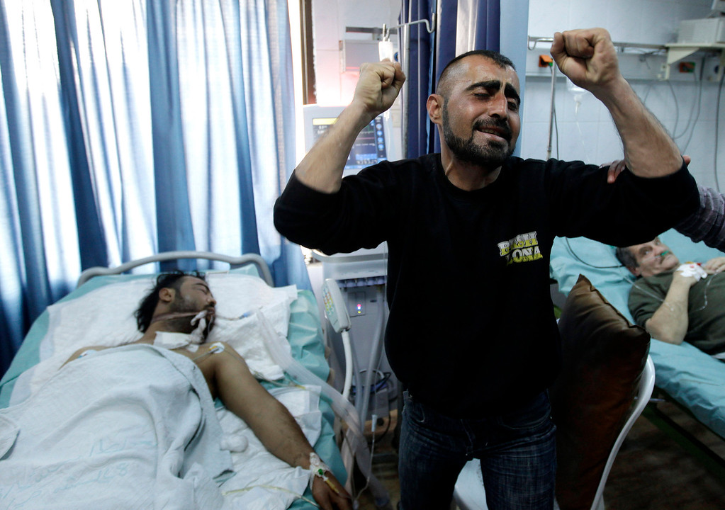 . FILE - A Syrian man reacts next to his brother, who was seriously wounded during a violence between security forces and armed groups in Latakia, northwest of Damascus, Syria, on Sunday, March 27, 2011. (AP Photo/Hussein Malla, File)