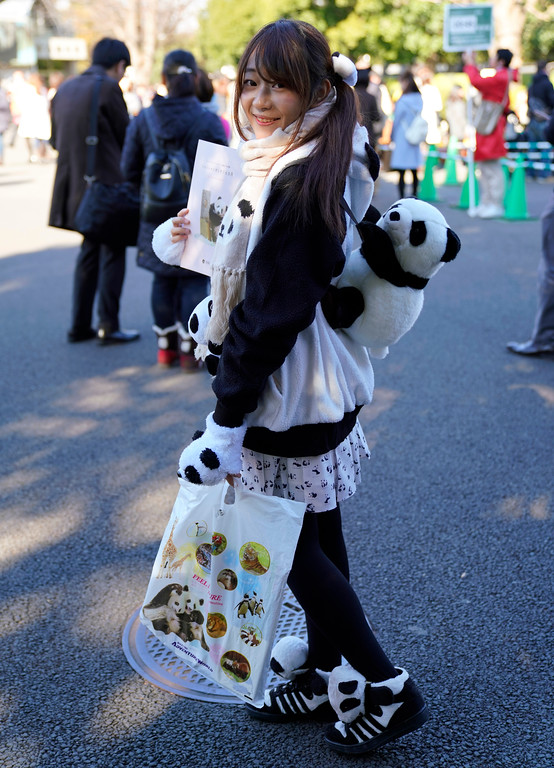 . Saeko Nishitani, 23, wearing clothes featuring pandas poses for a photo at Ueno Zoo during a public viewing of female giant panda cub Xiang Xiang in Tokyo, Tuesday, Dec. 19, 2017. Xiang Xiang, which means fragrance in Chinese, was born in June at Tokyo�s Ueno Zoo to its resident panda. It�s a first one in 39 years to have been born in Ueno, known as a panda town. The zoo and its neighborhood celebrated Xiang Xiang�s healthy growth especially after the death of a days-old baby panda five years ago. (AP Photo/Shizuo Kambayashi)