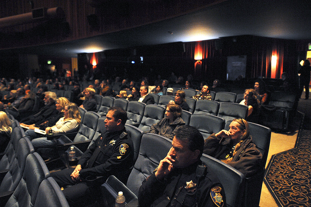 . Salinas Police Officers sit among community members Thursday at the Del Mar Theatre where a live broadcast of the memorial service for detectives Sgt. Loran \'Butch\' Baker and Elizabeth Butler was aired (Matthew Hintz/Sentinel).