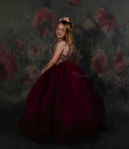 madelyn standing sideays smiling at camera with floral texture. marron gown. low res.jpg