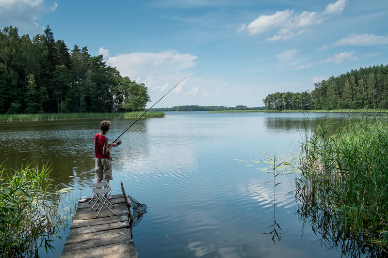 Boy fishing from a wooden pier, Giby, Poland
