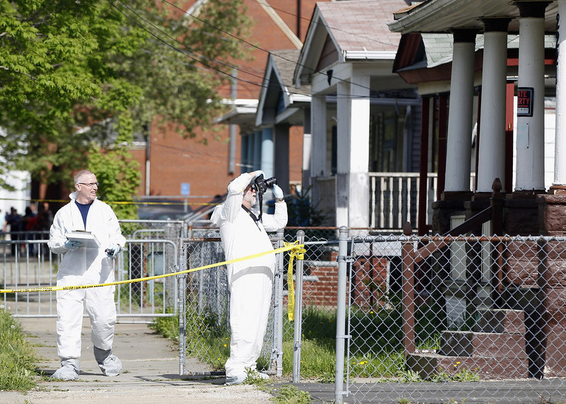 . Police in protective suits investigate houses down the street from the house where three women were held captive for close to a decade May 8, 2013 in Cleveland, Ohio. Amanda Berry, Gina DeJesus, and Michelle Knight managed to escape their captors on May 6, 2013. Ariel Castro was charged with kidnap and rape.   (Photo by Matt Sullivan/Getty Images)