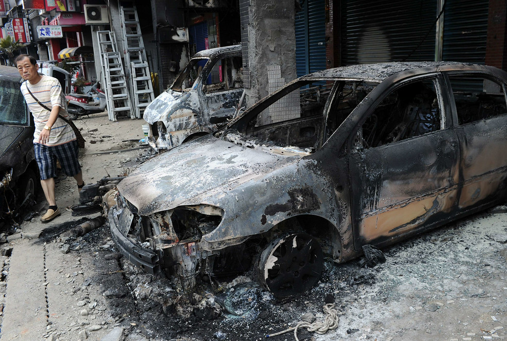 . A man walks past damaged cars after the gas explosions in southern Kaohsiung on August 1, 2014.  A series of powerful gas blasts killed at least 24 people and injured up to 271 in the southern Taiwanese city of Kaohsiung, overturning cars and ripping up roads, officials said.  AFP PHOTO / SAM YEH/AFP/Getty Images