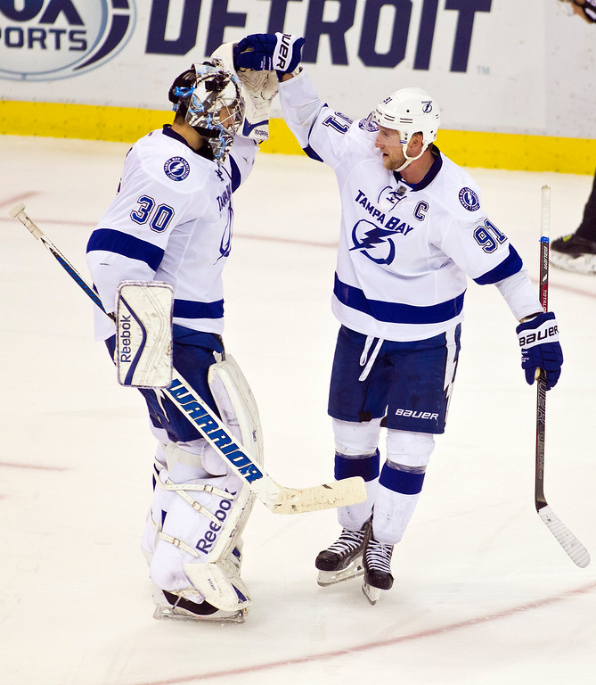 . Tampa Bay Lightning goalie Ben Bishop (30) celebrates with forward Steven Stamkos (91) after a 4-3 victory of an NHL game against the Detroit Red Wings in Detroit, Mich., Sunday, Nov. 9, 2014. (AP Photo/Tony Ding)