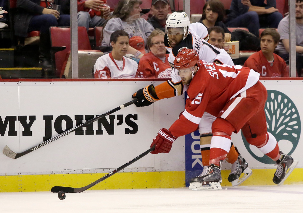 . Detroit Red Wings\' Riley Sheahan (15) keeps the puck away from Anaheim Ducks\' Devante Smith-Pelly (12) during the first period of an NHL hockey games Saturday, Oct. 11, 2014, in Detroit. (AP Photo/Duane Burleson)