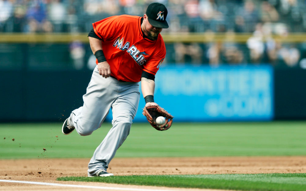 . Miami Marlins third baseman Casey McGehee fields a single off the bat of Colorado Rockies\' Josh Rutledge in the first inning of a baseball game in Denver on Sunday, Aug. 24, 2014. (AP Photo/David Zalubowski)