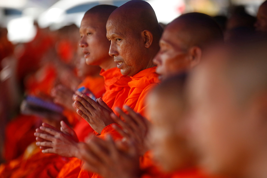 . Thai Buddhist monks pray for 12 boys and their soccer coach went missing, in Mae Sai, Chiang Rai province, in northern Thailand, Sunday, July 1, 2018. Thai navy divers leading the search for the boys and their soccer coach in a cave have failed to make much headway in their effort to push through the murk of a kilometer- (half-mile-) long chamber to what is believed to be a clear area leading to where the missing may be sheltering, officials said.(AP Photo/Sakchai Lalit)