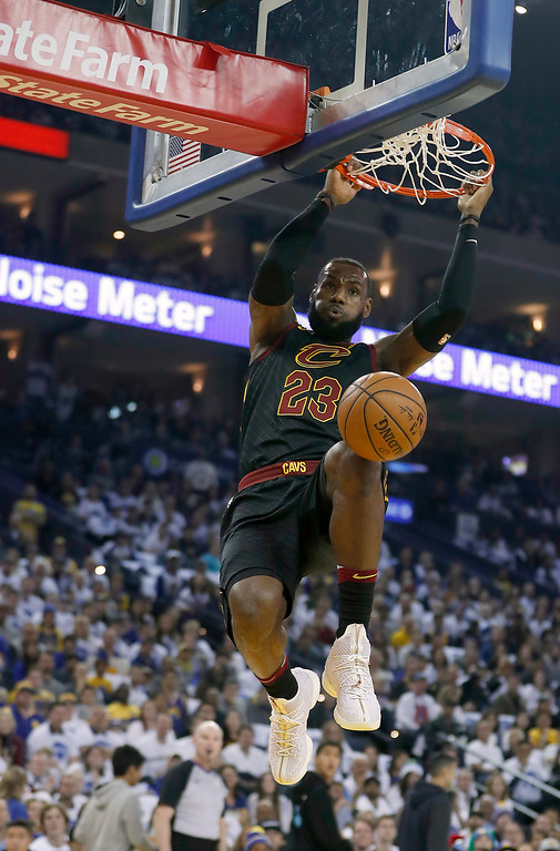. Cleveland Cavaliers forward LeBron James (23) dunks against the Golden State Warriors during the first half of an NBA basketball game in Oakland, Calif., Monday, Dec. 25, 2017. (AP Photo/Tony Avelar)