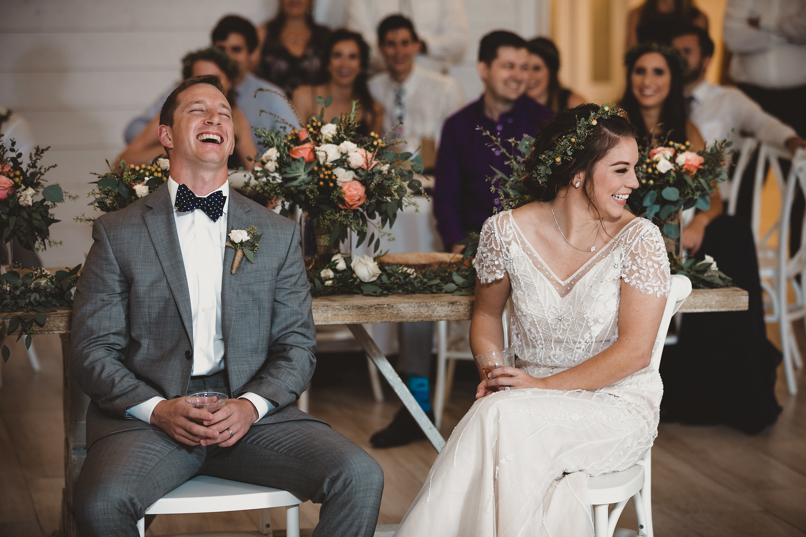 A bride and groom laughing together during wedding speeches