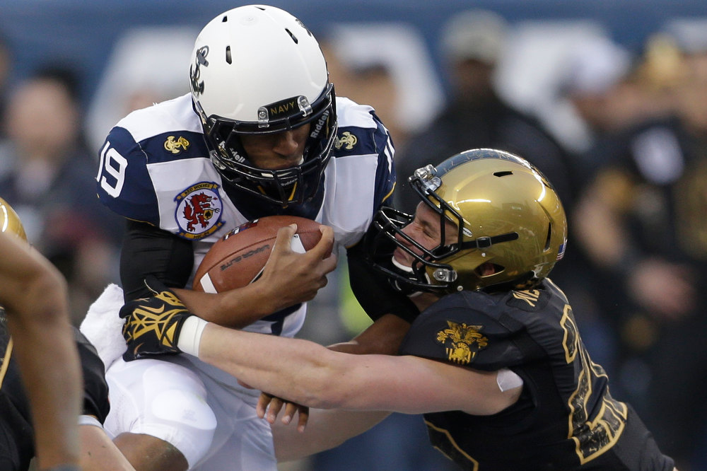 . Navy quarterback Keenan Reynolds runs the ball as Army Robert Kough linebacker tackles him during the first half of an NCAA college football  game Saturday, Dec. 8, 2012, in Philadelphia. (AP Photo/Matt Rourke)