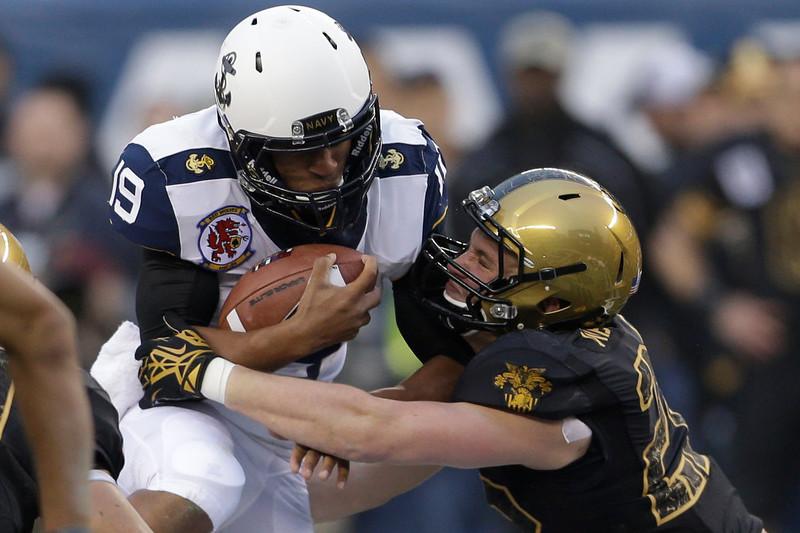 . Navy quarterback Keenan Reynolds runs the ball as Army Robert Kough linebacker tackles him during the first half of an NCAA college football  game Saturday, Dec. 8, 2012, in Philadelphia. (AP Photo/Matt Rourke)
