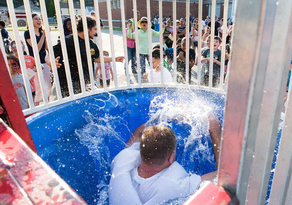06/08/18 Wesley Bunnell | Staff Vance Elementary School held an end of the year celebration on Friday night for students and parents. Jeff Petillo, husband of a Vance teacher, falls into the dunk tank as spectators laugh.