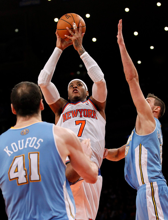 . New York Knicks forward Carmelo Anthony drives to the basket defended by Denver Nuggets forward Danilo Gallinari and center Kosta Koufos (L) in the fourth quarter of their NBA basketball game at Madison Square Garden in New York, December 9, 2012.    REUTERS/Adam Hunger