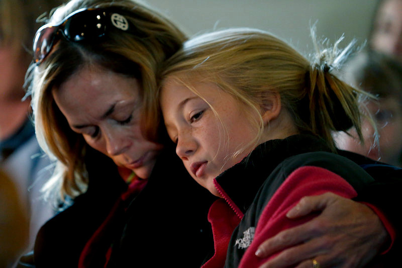 . Molly Delaney, left, holds her 11-year-old daughter, Milly Delaney, during a service in honor of the victims who died a day earlier when a gunman opened fire at Sandy Hook Elementary School in Newtown, Conn., as people gathered at St. John\'s Episcopal Church , Saturday, Dec. 15, 2012, in the Sandy Hook village of Newtown, Conn. The massacre of 26 children and adults at Sandy Hook Elementary school elicited horror and soul-searching around the world even as it raised more basic questions about why the gunman, 20-year-old Adam Lanza, would have been driven to such a crime and how he chose his victims.  (AP Photo/Julio Cortez)