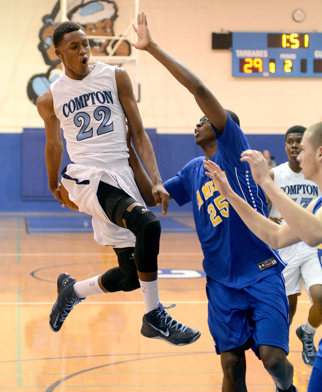 . Compton\'s Isaiah Bailey (22) makes a pass behind his back, faking the shot, behind La Mirada\'s Dezmon Murphy (25) in a first round CIF Division 3AAA basketball game Wednesday night in Compton. 20130213 Photo by Steve McCrank / Staff Photographer