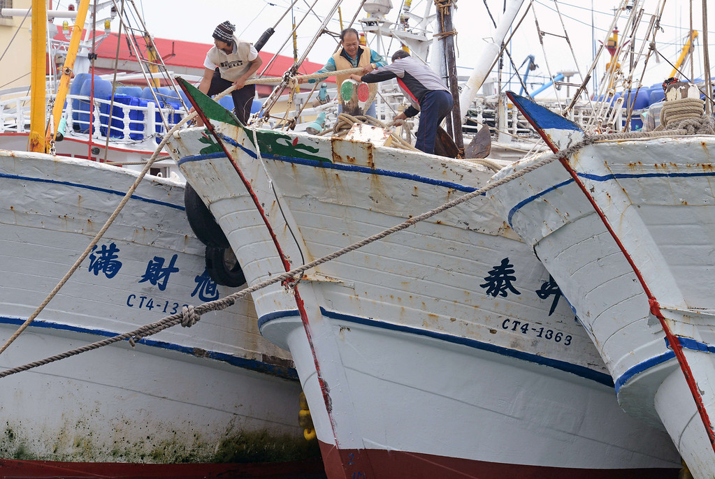 . Foreign fish workers tie a boat at the Patoutze fish harbor, in Keelung, northern Taiwan on October 5, 2013. Taiwan on October 5 issued a warning over Typhoon Fitow as it approached the island\'s north with threats of torrential rains and powerful winds over the weekend.  SAM YEH/AFP/Getty Images