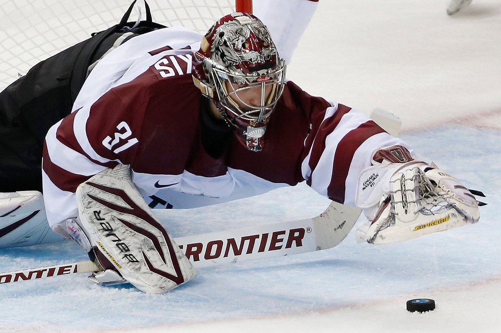 . Latvia goaltender Edgars Masalskis dives for a puck in front of the net during the third period of the 2014 Winter Olympics men\'s ice hockey game against Switzerland at Shayba Arena, Wednesday, Feb. 12, 2014, in Sochi, Russia. (AP Photo/Petr David Josek)