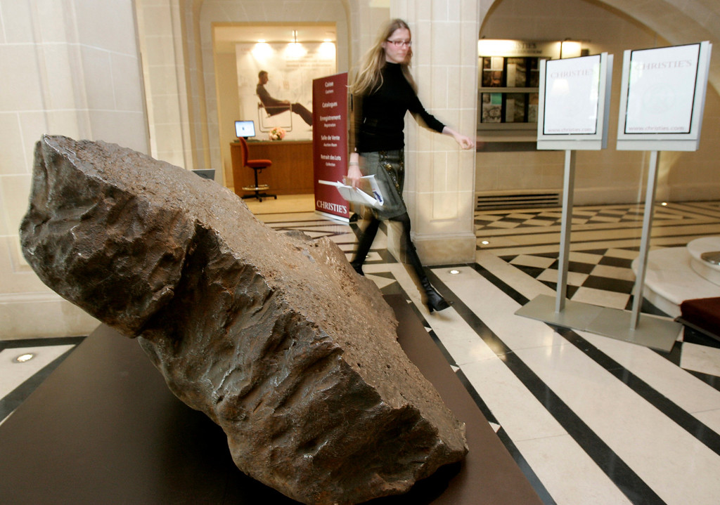 . A woman walks past the Seymchan meteorite at Christie\'s auction house in Paris, Wednesday, April 2, 2008. The 2.7-ton meteorite discovered in eastern Russia in 1967 will go on auction on April 16. (AP Photo/Francois Mori)