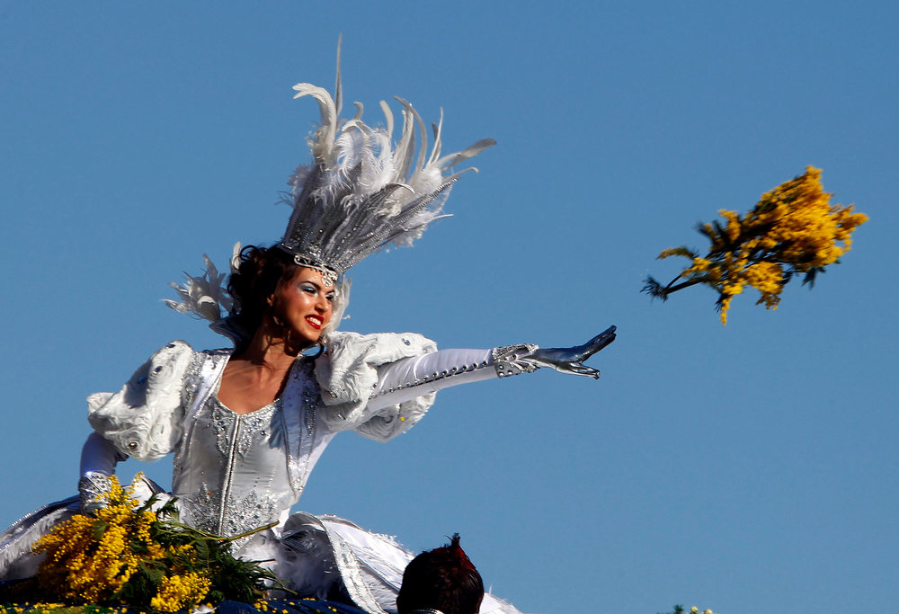 Description of . The Queen of the Carnival throws flowers during the Carnival parade in Nice February 16, 2013. The 129th Carnival of Nice runs from February 15 to March 6 and celebrates the