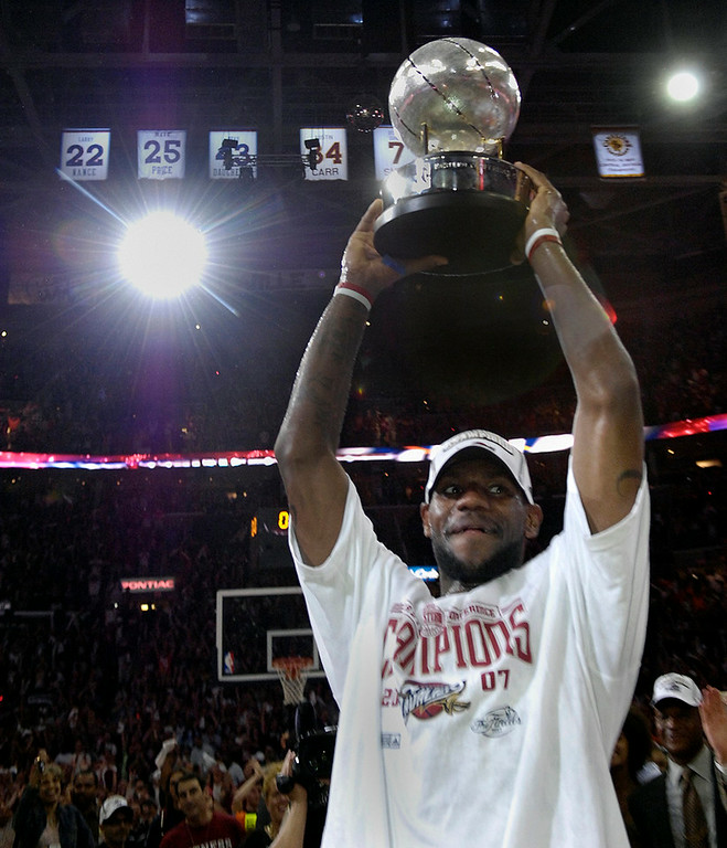 . Michael Blair/MBlair@News-Herald.com The Cavs LeBron James holds the Eastern Conference Topy high above his head as camera flashes light up the rafters containing the jerseys of other past Cavalier greats.