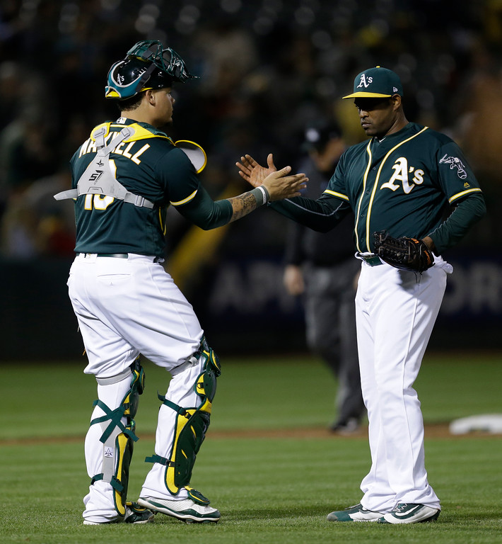 . Oakland Athletics\' Santiago Casilla, right, celebrates the team\'s 5-0 win over the Cleveland Indians with Bruce Maxwell at the end of the baseball game Friday, July 14, 2017, in Oakland, Calif. (AP Photo/Ben Margot)