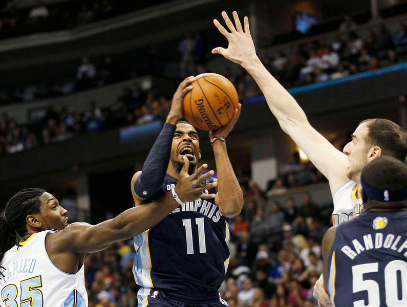 . Memphis Grizzlies guard Mike Conley (11) goes up for a shot against Denver Nuggets Kenneth Faried (L) and Kosta Koufos (R) in the first quarter of their NBA basketball game in Denver December 14, 2012.   REUTERS/Rick Wilking
