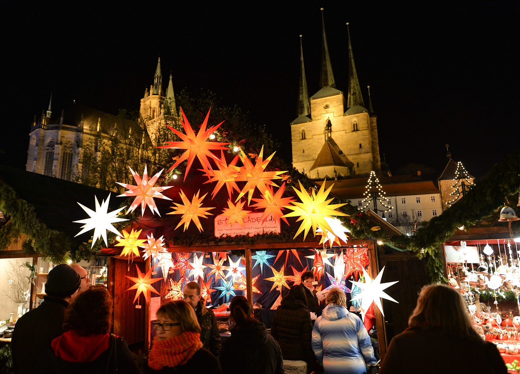 . Visitors walk past a stand that sells glowing stars at the Christmas market in Erfurt, Germany, 26 November 2013. In the background is the Erfurt Cathedral (L) and the church St. Severi (R).  EPA/Marc Tirl