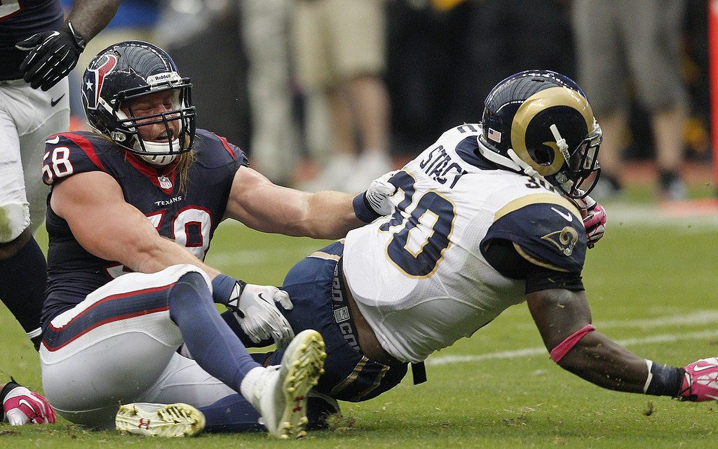 . Zac Stacy #30 of the St. Louis Rams drags Brooks Reed #58 of the Houston Texans as he tries to tackle him at Reliant Stadium on October 13, 2013 in Houston, Texas.  (Photo by Bob Levey/Getty Images)