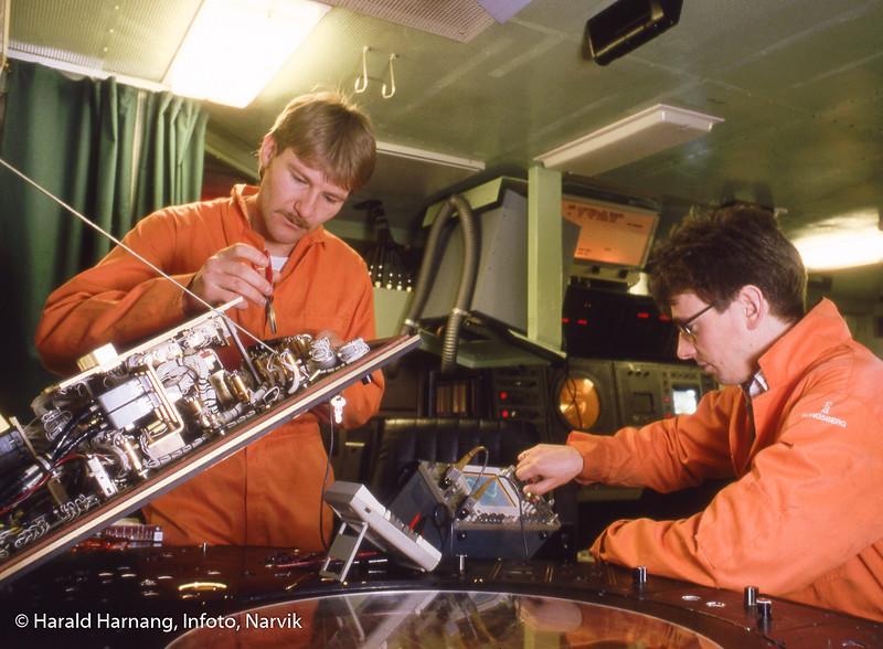 Kongsberg Våpenfabrikk, Narvik, trolig ombord på et marineskip, der man jobber med kalibrering av utstyr. Service på NAVKIS, installasjon på Kystvaktens Nordkapp-klasse. Til høyre Jan Kurt Johansen? og Nils ?