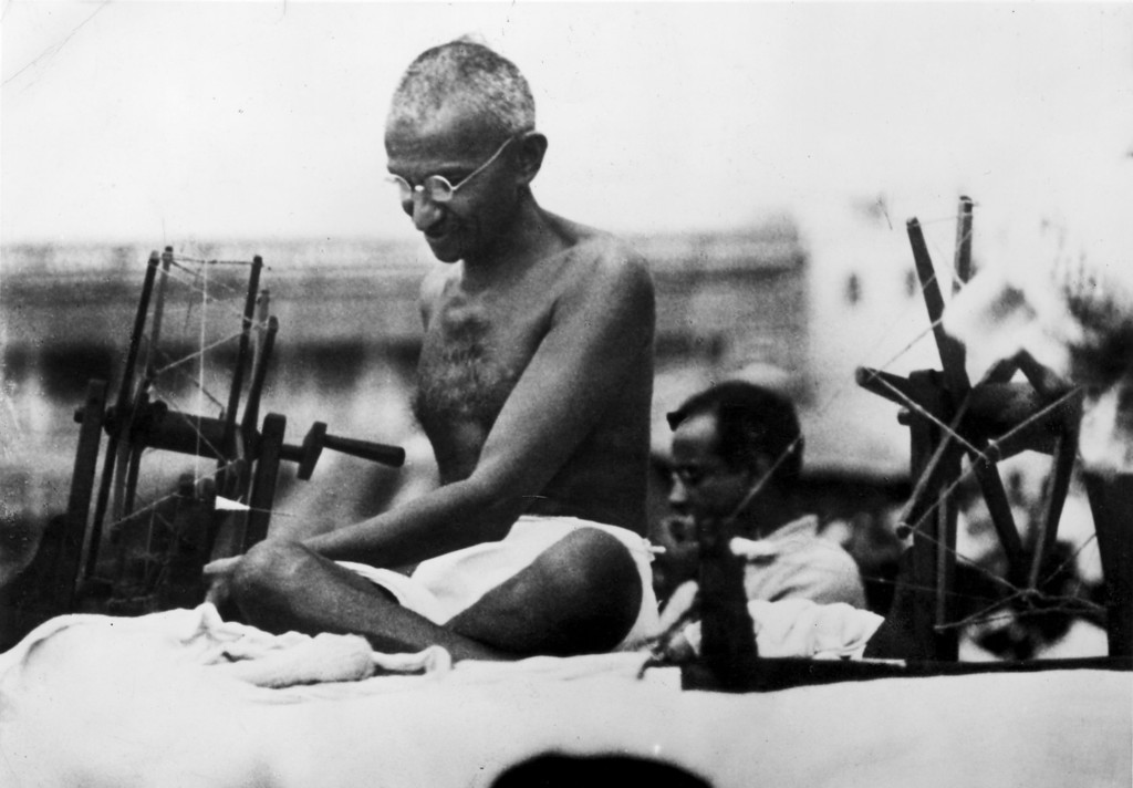 . Indian Nationalist leader Mahatma Gandhi (Mohandas Karamchand Gandhi, 1869 - 1948) at a spinning wheel during a \'Charlea\' demonstration in Mirzapur, Uttar Pradesh, 9th June 1925.  (Photo by Hulton Archive/Getty Images)