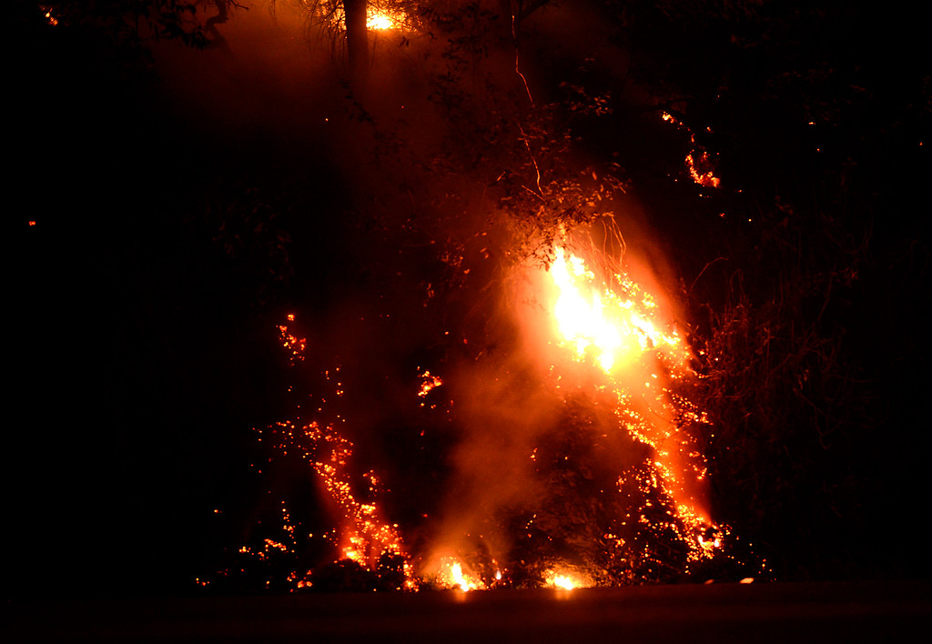 . Fire rolls down onto Highway 1 approximately 250 yards north of the Big Sur Station in Big Sur, Calif. on Tuesday December 17, 2013. (Photo David Royal/ Monterey County Herald)