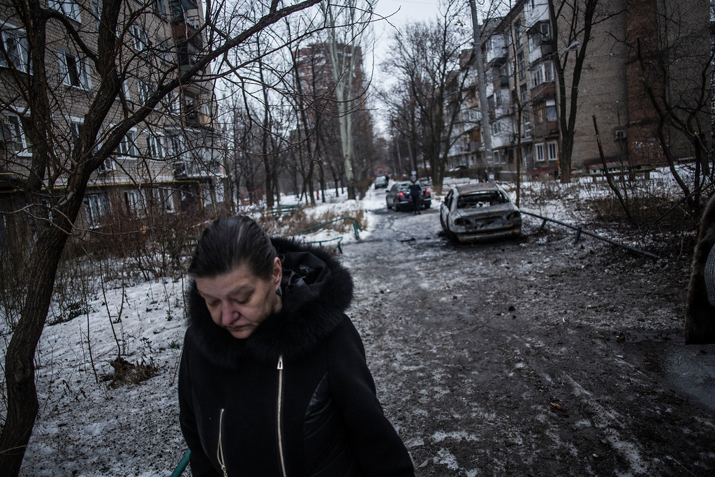 . A woman walks through a residential area hit by the Ukrainian Army Artillery in Voroshilovsky area, center of Donetsk, Ukraine. Sunday, Jan. 18, 2015. The separatist stronghold, Donetsk, was shaken by intense outgoing and incoming artillery fire as a bitter battle raged for control over the city\'s airport. Streets in the city, which was home to 1 million people before unrest erupted in spring, were completely deserted and the windows of apartments in the center rattled from incessant rocket and mortar fire. (AP Photo/Manu Brabo)