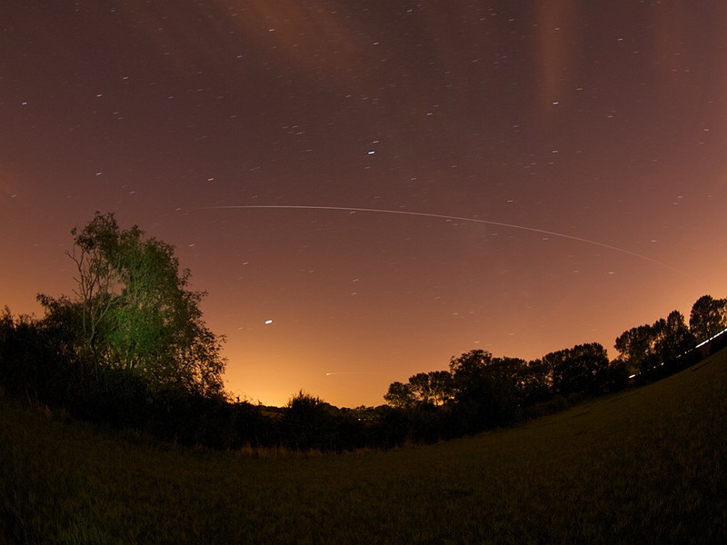 International Space Station (ISS) captured passing the Leics, UK skyline 2100hrs_10 Sep 09.Jupiter can be seen just to the right of the lit tree and below the path of the ISS. Really pleased with the capture.The ISS came into view to the sth and it looked like a fireball as it moved twds the Eastern earth shadow. In the sky. F3.5, 213s ISO 200 captured with Oly E3 & 8mm fisheye.