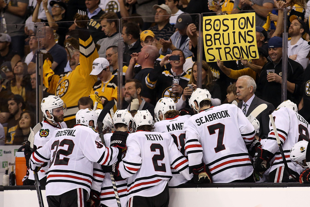 ". A Boston Bruins fan holds a ""Boston Bruins Strong\"" sign behind head coach Joel Quenneville  of the Chicago Blackhawks and his team in Game Three of the 2013 NHL Stanley Cup Final at TD Garden on June 17, 2013 in Boston, Massachusetts.  (Photo by Bruce Bennett/Getty Images)"