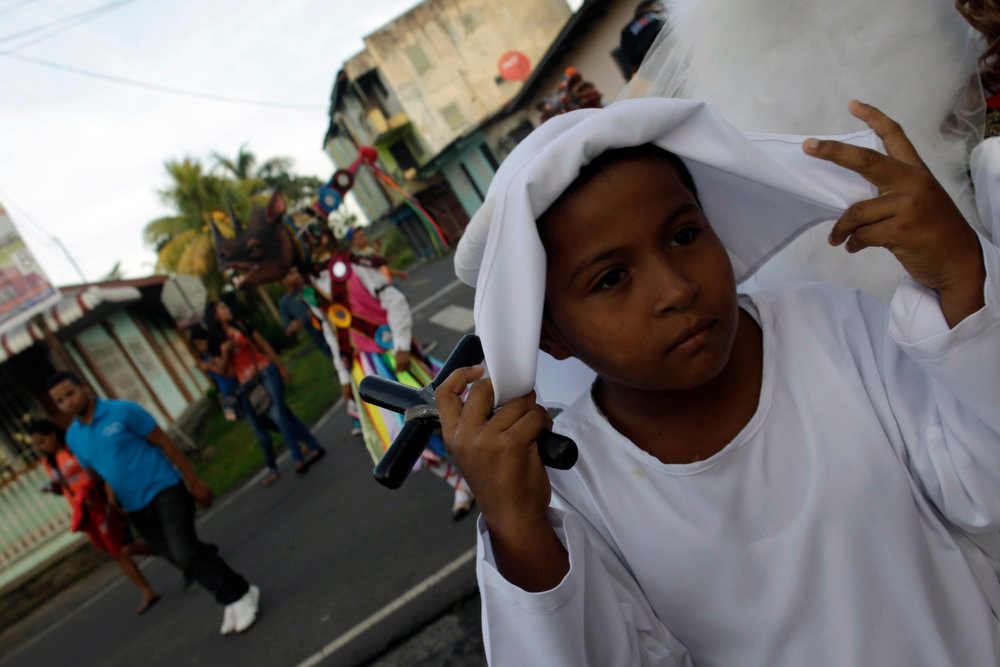 ". A boy dressed as a soul takes part in the annual Corpus Christi celebration in La Chorrera on the outskirts of Panama City May 30, 2013. During the annual celebration, people dressed as colorful devils, angels and souls dance the ""El Baile del Gran Diablo\"" (the Great Devil Dance), representing the struggle between good and evil, in a mixture of Spanish and indigenous traditions. REUTERS/Carlos Jasso"