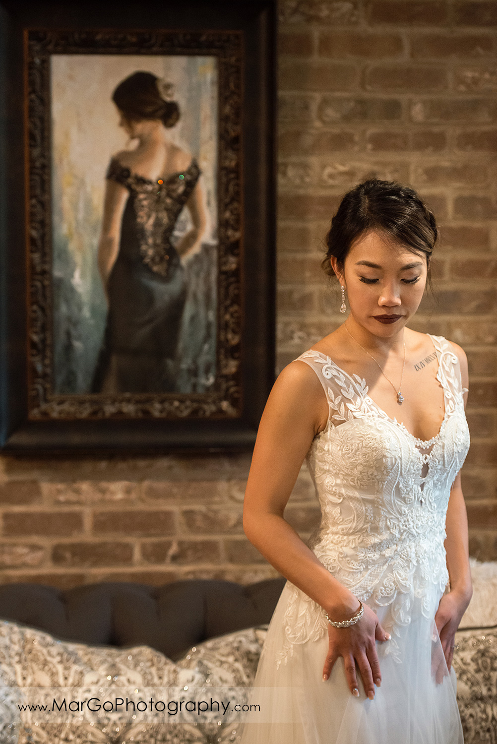 portrait of the bride with painting in background at Sunol's Casa Bella bridal suite