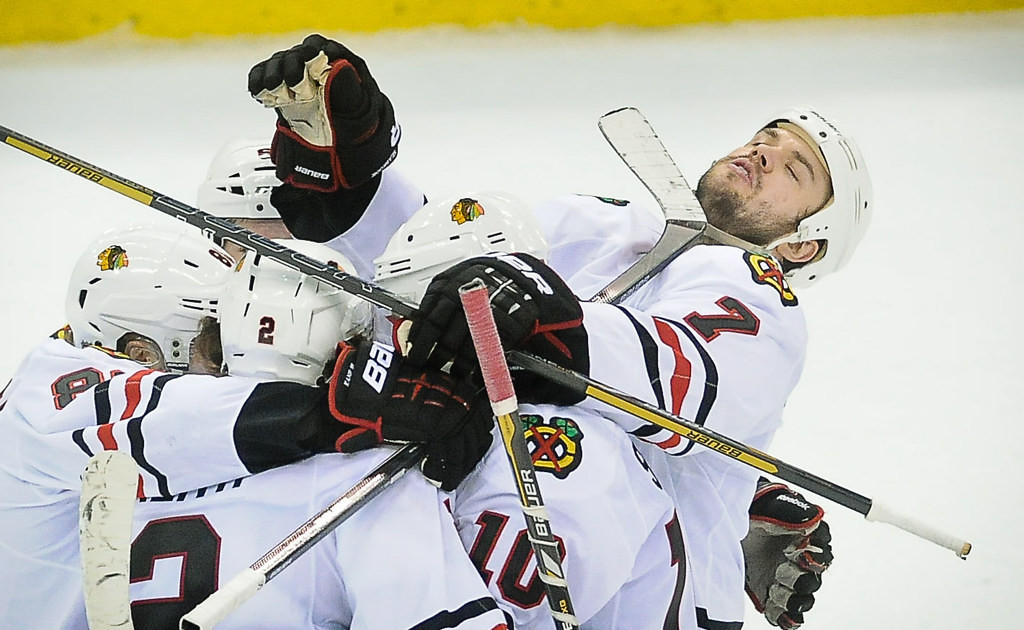 . Chicago defenseman Brent Seabrook, right, gets a high stick to the face while celebrating a goal by teammate Duncan Keith, left, in the third period against the Wild.  (Pioneer Press: Ben Garvin)
